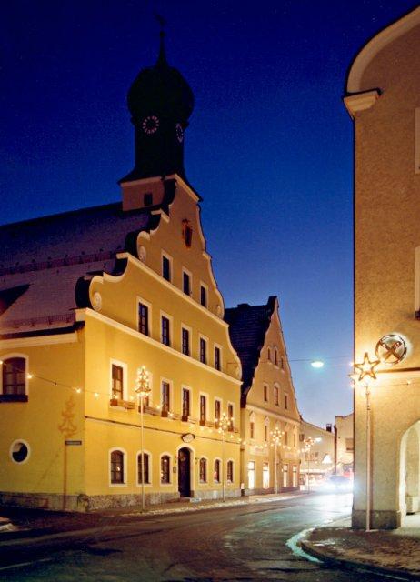 Das Rathaus der Stadt Grafing b.München bei Abenddämmerung, von den Straßenlaternen in orangenes Licht getaucht vor dem dämmernden, tiefblauen Himmel.